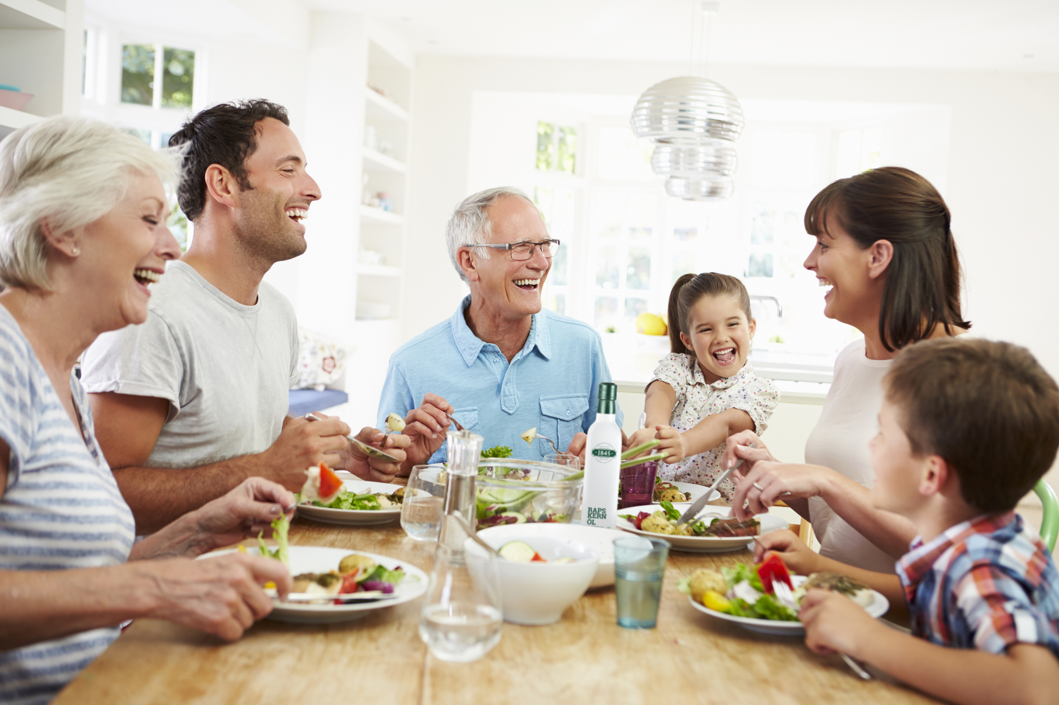 Multi Generation Family Eating Meal Around Kitchen Table